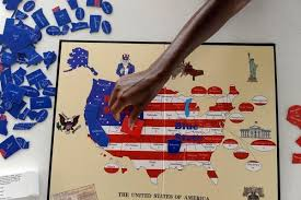 Sherri Pollard Places A Game Piece On The Red State Blue Board Created