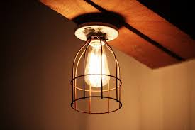 vintage industrial style porcelain light fixture with metal cage