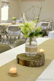 Mason Jar Centerpiece On Top Of Wood Slice Burlap Runner For Wedding