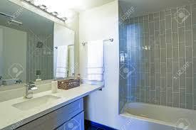 das warme und saubere badezimmer verfügt über eine duschwanne aus grauen glasfliesen und einen modernen waschtisch mit granitplatte