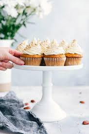 8 Carrot Cake Cupcakes On A Stand Positioned In Front Of Flowers