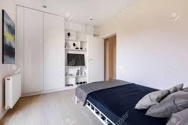 weißes schlafzimmer mit kleiderschrank bett bücherregal und moderner kunst