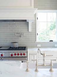Smoke Gray Glass Subway Tile Backsplash White Cabinets And Carrera Marble Countertops