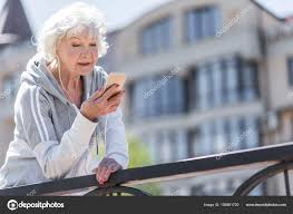 Happy Nice Elderly Woman Having Relax Time While Exercising Outdoors Stock Photo