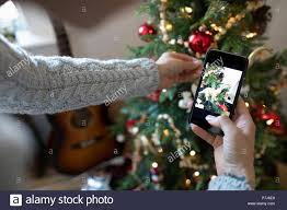 Young Woman With Camera Phone Decorating Apartment Christmas Tree