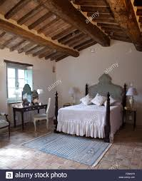 White Bedcover On Bed With Turned Spindles In Italian Country Bedroom Rustic Wooden Beamed Ceiling