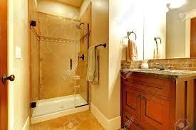 badezimmer mit holzgehäuse und fliesen dusche mit goldenen ton