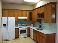 Maple Shaker Cabinets With White Counters And Appliances
