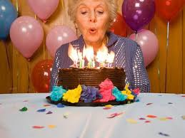 Senior woman blowing out candles on cake