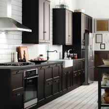 A Large Kitchen With Black Brown Drawers And Doors Shown Together Stainless Steel