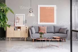 großes bild auf eine graue wand oben ein elegantes sofa mit kissen in einem stilvollen wohnzimmer interieur mit kupfer möbel stockfoto und mehr bilder