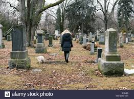 A Woman And Dog Walking Through Cemetery On Gloomy Day