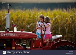 Caledonia Pumpkin Patch by Two Young Girls Play On A Tractor During A Visit To Country