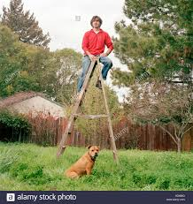 Man Standing On A Ladder In His Backyard With His Dog Sitting On ... Dog Leashes Leads Best For Pets Petco How To Make A Leash Holder Leash Holder And Quadpro Retractable Leashpet Lead 315 Inches For Urpower 164 Feet Nylon Official A Guide Buying The Rover Blog Installation Of Cable Run Youtube Offleash Dog Bar Opens In Fairhaven Tap Trail Side Yard Solution Pet Friendly Xgrass Artificial Turf Run The Dog Yard Aliexpresscom Buy Traction Rope 2017 Abs Large Handle April 2012 Backyard Beyond Fence Borders Tips About Safety