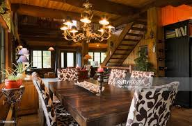 Dining Room With Wooden Table And Upholstered Chairs Inside A Cottage Style Log Home Quebec