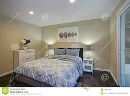 schlafzimmer des zweiten stocks mit taupewänden blaues bett