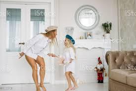 junge lustige glückliche faire lange haare und ihr süßes mädchen spaß zusammen tanzen im wohnzimmer glücklich familie lebensstil stockfoto und