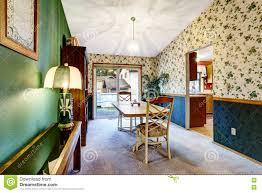 grünes wohnzimmer mit blumentapete braunem kabinett und