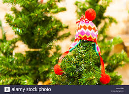 Small Red Childrens Hat Hanging On Christmas Tree Bright Green Background