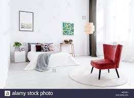 rote sessel auf runden teppich in weiß schlafzimmer