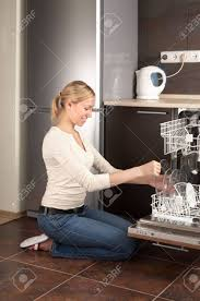 The Blonde Sits Near To Open Dishwasher On Kitchen Stock Photo