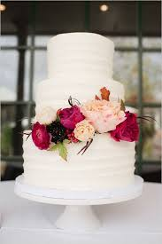 white wedding cake with red flowers
