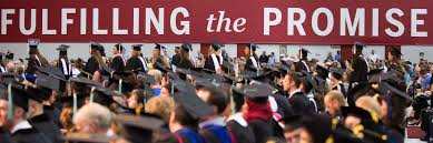 Graduates In Caps And Gowns Sit By A Banner That Reads Fulfilling The Promise
