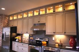 artistic lighting above kitchen cabinets using soft yellow led