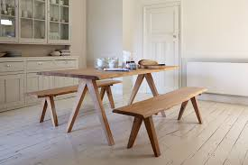 minimalist wooden kitchen table with tapered legs and two benches