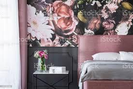 graukissen auf rosa bett neben tisch mit blumen im schlafzimmer innenraum mit tapete echtes foto stockfoto und mehr bilder bett