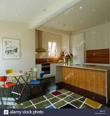 mehrfarbige lehrstühle an hellen holztisch in moderne küche