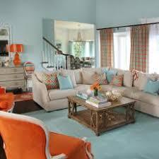 light blue coastal living room with orange armchairs beige