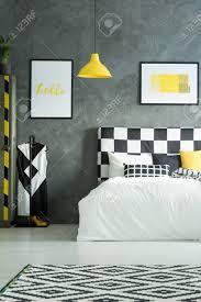 zwei bilder über kingsize bett im schwarz weißen schlafzimmer mit gelben elementen