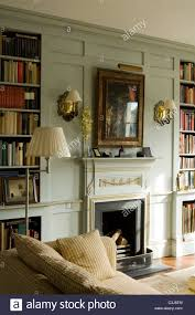 Regency Style Fireplace Flanked By Open Book Shelving In Living Room With Wall Sconces