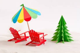 Made From Paper Christmas Tree Beach Chair And Umbrella In The Sand White Background