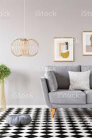 kissen platziert auf dem schachbrett linoleumboden in grau wohnzimmer interieur mit gold le mit kissen und zwei moderne poster an der wand