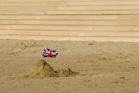 A Simple Sand Castle With Union Jack Stuck In It