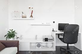 moderne wohnzimmer mit schreibtisch und computer dem bildschirm sofa und tisch mit weißem teppich auf dunkelbraunen holzboden