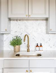 gray cabinets with marble chevron tile backsplash transitional
