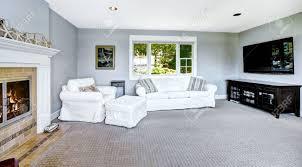 hellblau wohnzimmer mit weißen sofa sessel tv und gemütlichen kamin