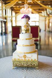 A Six Tiered Lemon Cake With Butter Cream Frosting Embellished Gold Accents And Purple