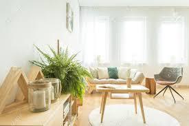 nahaufnahme kerzen und farn auf einem schrank im gemütlichen wohnzimmer mit holztisch auf weißem teppich