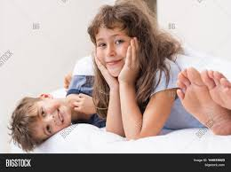 happy children in pajamas lying on bed and looking at camera feet