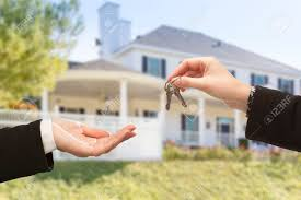 Handing Over The New House Keys With Home In Background Stock Photo