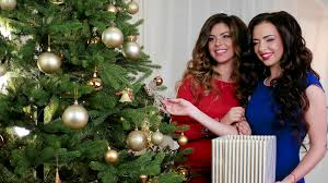 Happy New Year Girls In Evening Dresses Talk Laugh During Decorating A Christmas Tree Preparing For The Holiday Party On Hanging