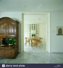 Antique Cupboard In Modern White Hall With Marble Tiled Floor And View Of Dining Room Through Open Double Doors