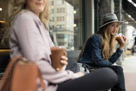 Young Women Friends Drinking Iced Coffee On Bench At Sidewalk Cafe