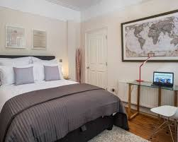This Is An Example Of A Classic Bedroom In London With Beige Walls And Medium Hardwood