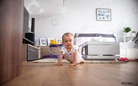 foto auf lager baby geht im hellen wohnzimmer auf allen vieren unter