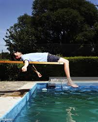 Young Man Basking On Diving Board Side View Stock Photo